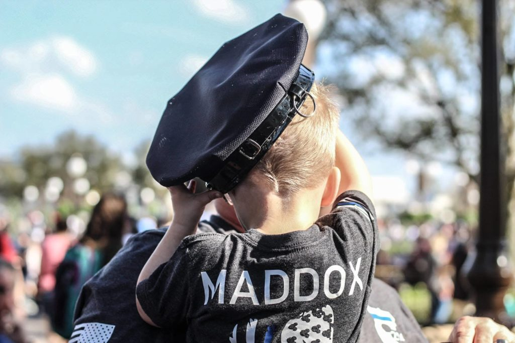 A little boy with the name Maddox on the back of his shirt.