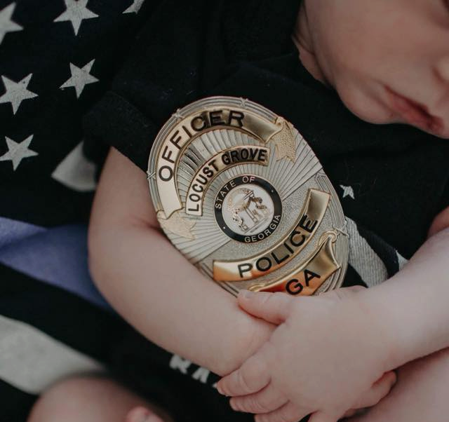 A baby holding a police badge