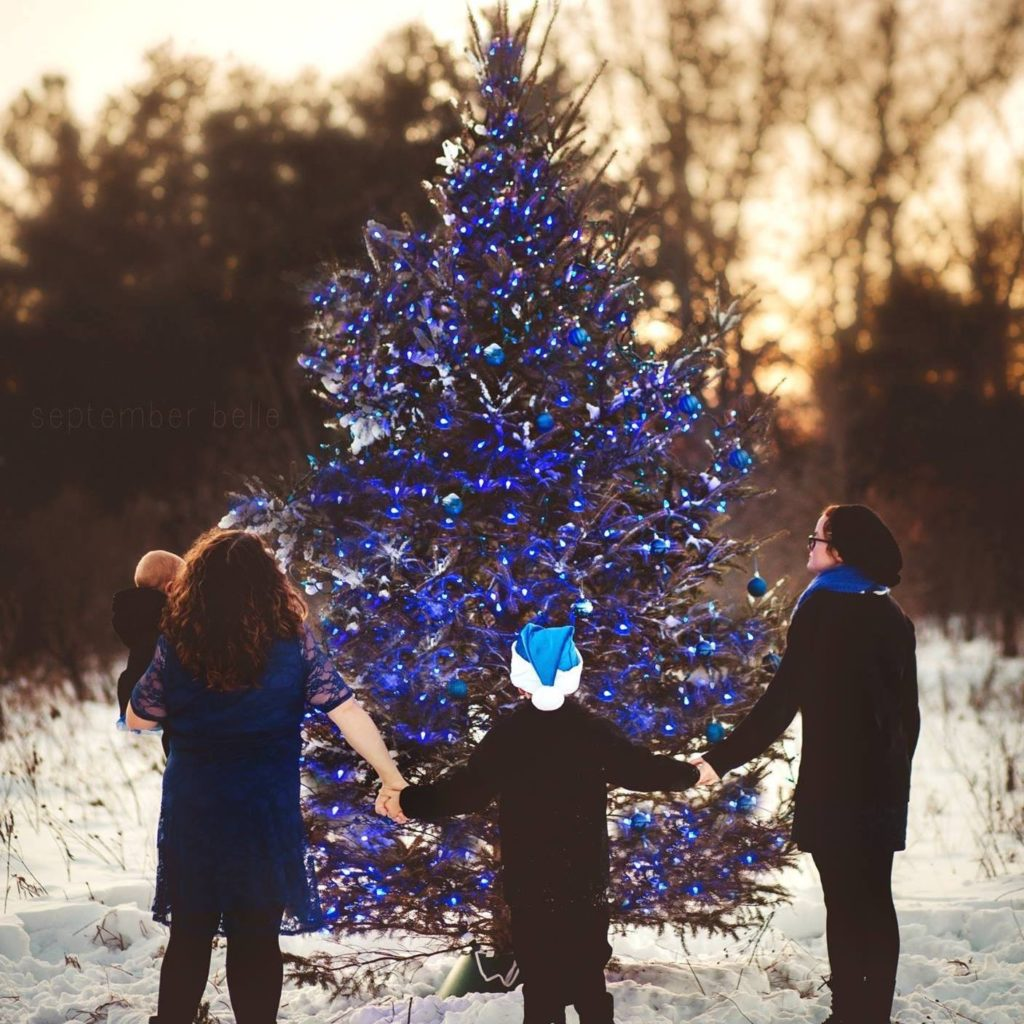 The glaze family holding hands in front of a christmas tree.